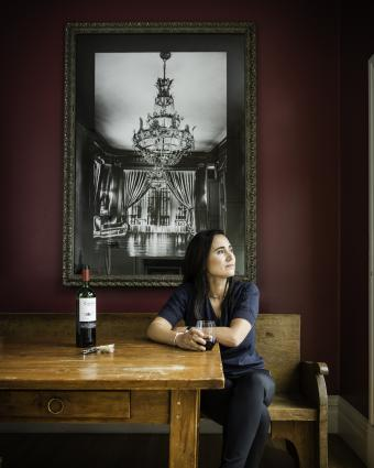 Laura Catena sits at a table with a glass of wine