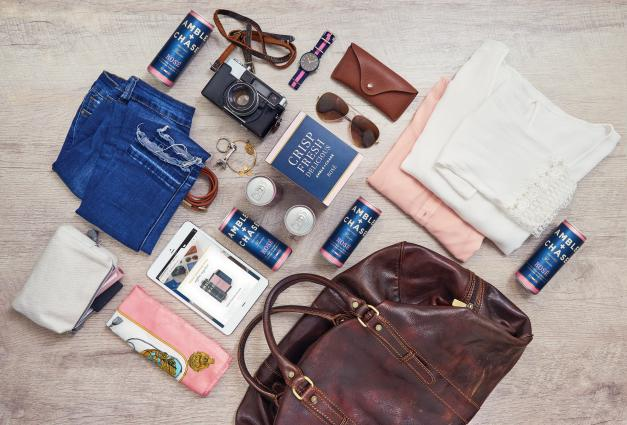 AMBLE + CHASE vacation essentials laid out on backdrop